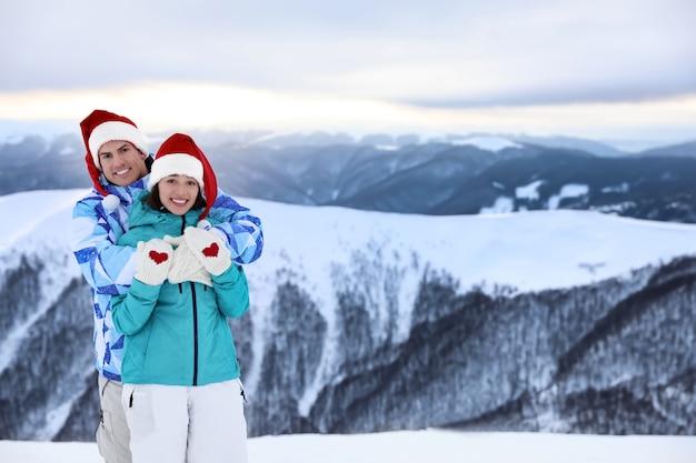 Casal feliz usando luvas quentes e gorros de papai noel em um resort nevado