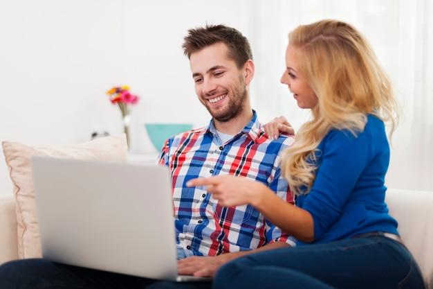 Casal feliz usando o computador em casa