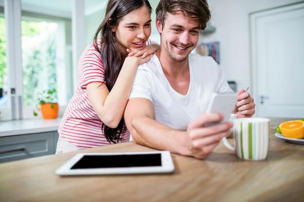 Casal feliz usando smartphone na cozinha