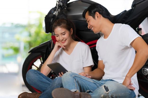 Casal feliz usando tablet digital em casa com um fundo de motocicleta