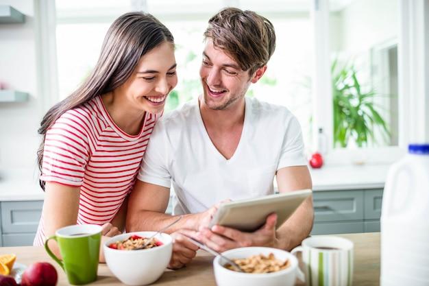 Casal feliz usando tablet e tomando café da manhã na cozinha