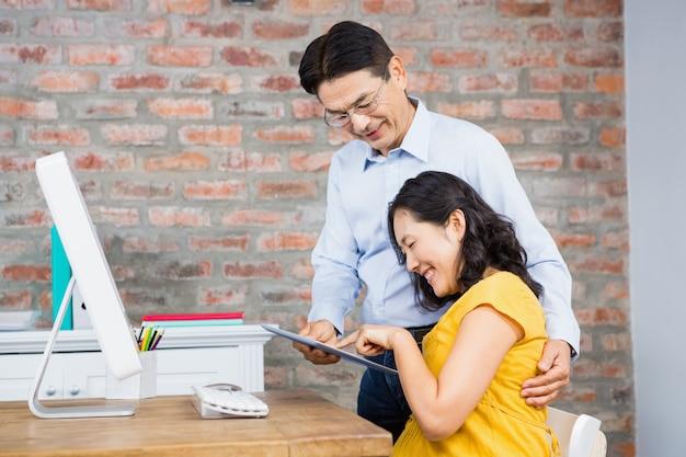 Casal feliz usando tablet em casa