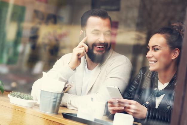 Casal feliz usando telefones em restaurante