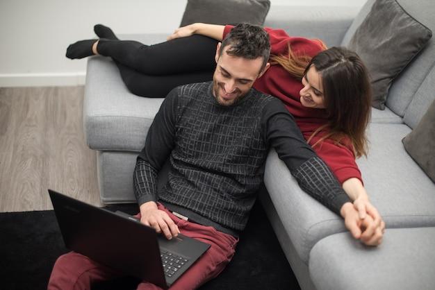 Casal feliz usando um computador portátil em sua casa