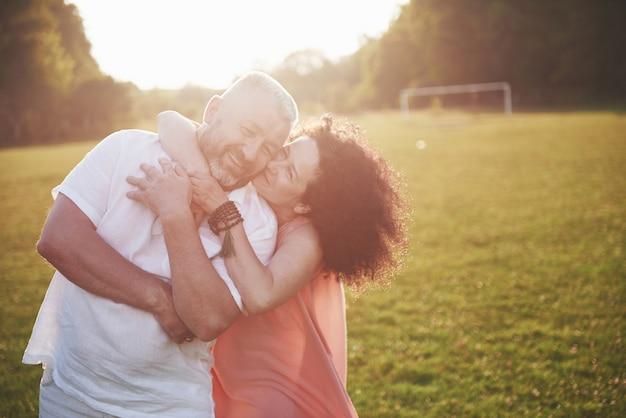 Casal feliz verão velho sorrindo para o parque em um dia ensolarado.
