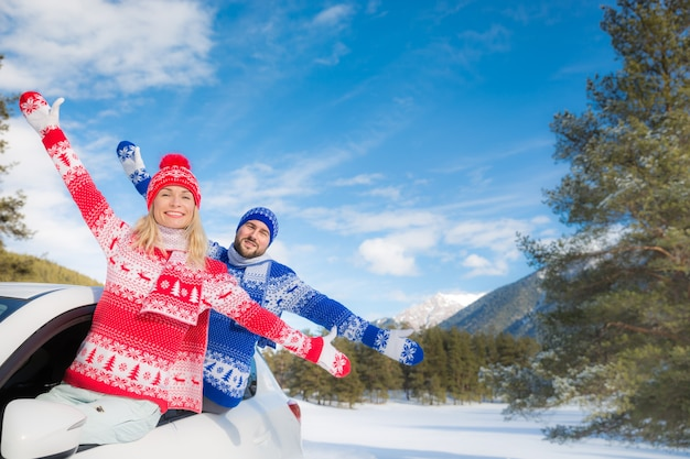 Casal feliz viaja de carro amigos se divertindo nas montanhas, mulher e homem nas férias de inverno