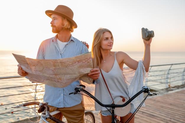 Casal feliz viajando no verão de bicicleta, olhando no mapa e tirando fotos