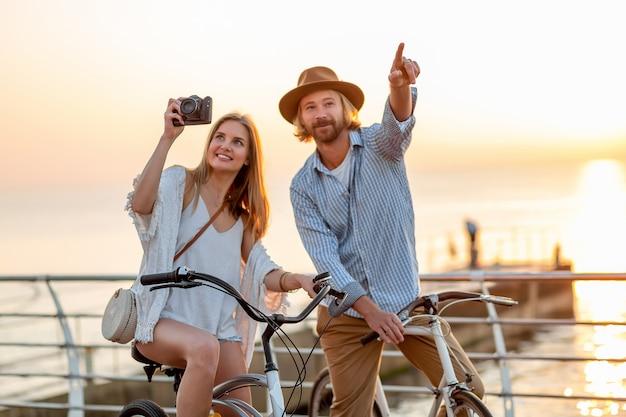 Casal feliz viajando no verão de bicicleta, tirando fotos