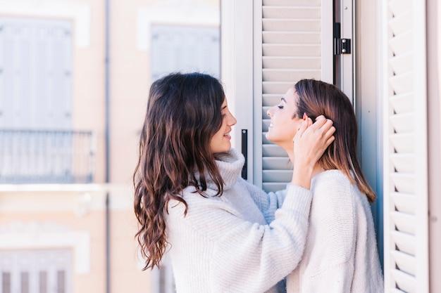 Casal feminino gentil se beijando na varanda