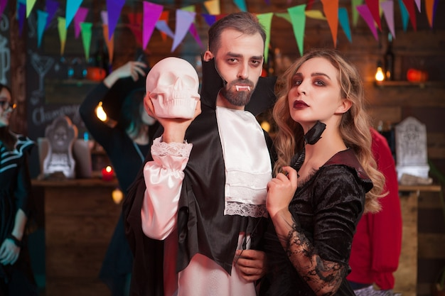 Casal fervoroso em fantasias de halloween em uma festa. homem vestido de drácula para a celebração do dia das bruxas.