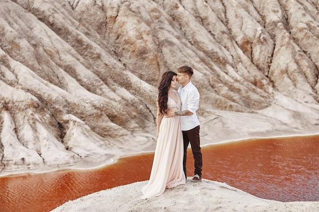 Casal fica no precipício da montanha e do lago vermelho e abraçando