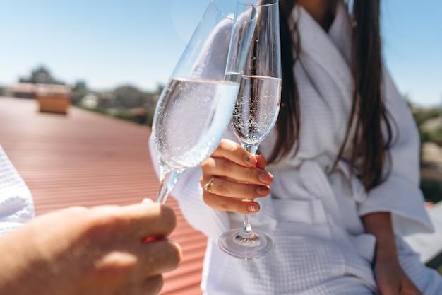 Casal flertando com vinho espumante no telhado