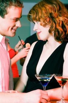 Casal flertando em uma festa