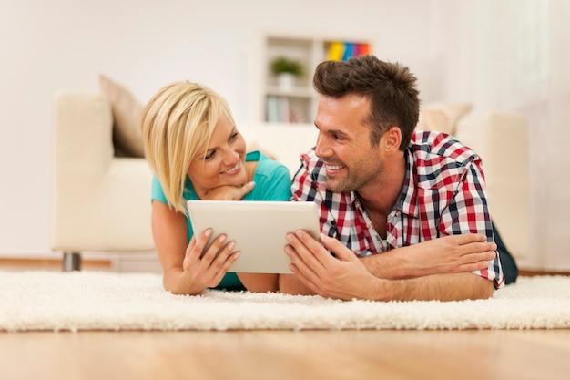 Casal flertando usando tablet digital em tapete na sala de estar