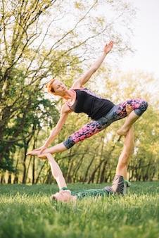 Casal flexível praticando acro yoga no parque