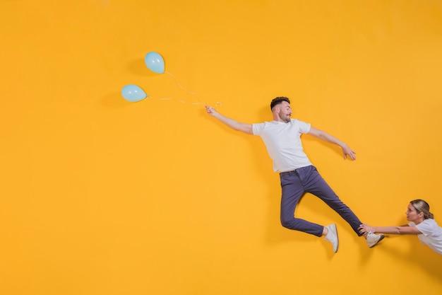 Casal flutuando no ar com balões