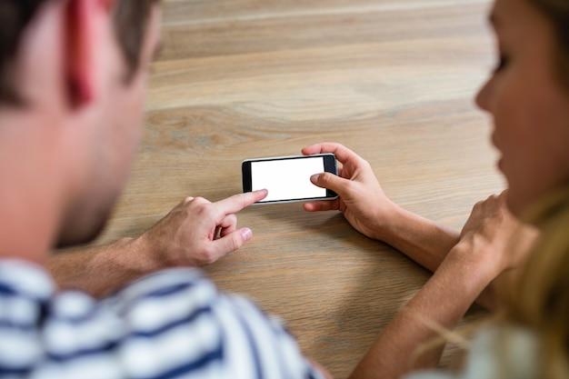 Casal focado usando smartphone em casa