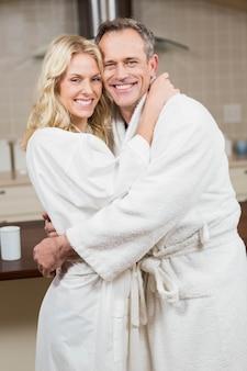 Casal fofo abraçando em roupões de banho na cozinha