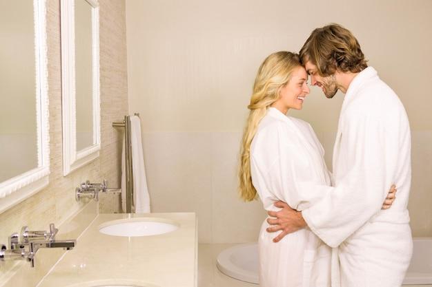 Casal fofo abraçando no roupão de banho no banheiro em casa