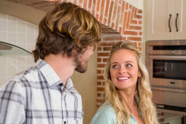 Casal fofo amorosamente olhando uns aos outros na cozinha