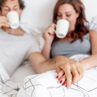 Casal fofo bebendo café na cama turva fundo