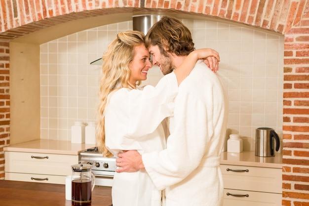 Casal fofo carinhos em roupões na cozinha