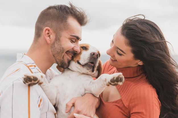 Casal fofo com cachorro na beira-mar