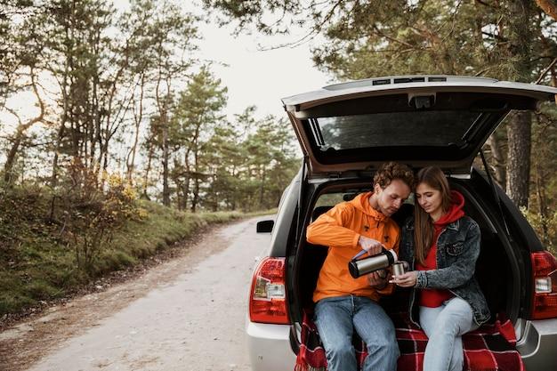 Casal fofo curtindo uma bebida quente no porta-malas do carro