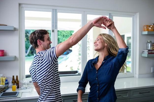 Casal fofo dançando na cozinha