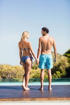 Casal fofo de mãos dadas à beira da piscina