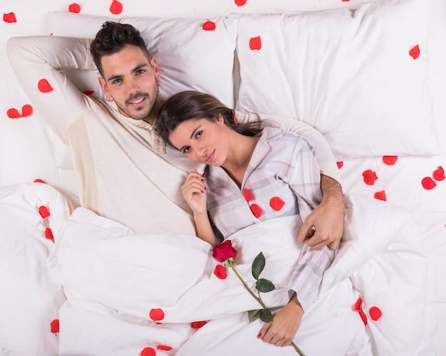 Casal fofo deitado na cama com pétalas de rosa