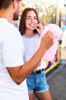 Casal fofo, desfrutando de algodão doce rosa