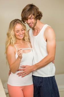 Casal fofo esperando o resultado do teste de gravidez no banheiro