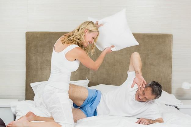 Casal fofo jogando travesseiro lutar na cama
