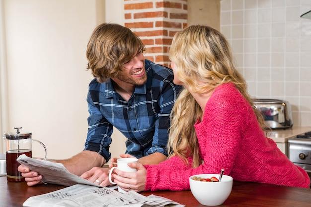 Casal fofo lendo o jornal na cozinha