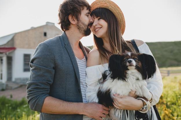Casal fofo, muito elegante, hipster apaixonado, caminhando com um cachorro no campo