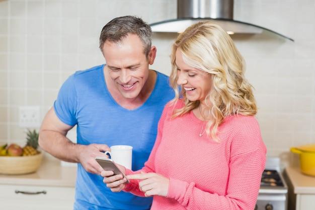 Casal fofo olhando para smartphone na cozinha