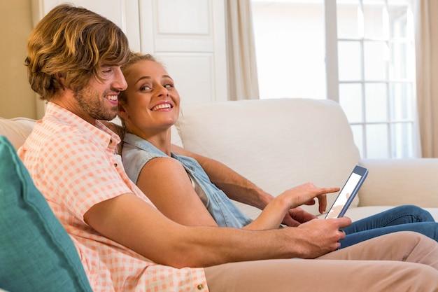 Casal fofo olhando tablet sentado no sofá na sala de estar