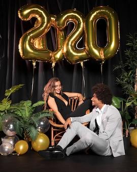 Casal fofo olhando um ao outro cercado por balões com 2020 ano novo