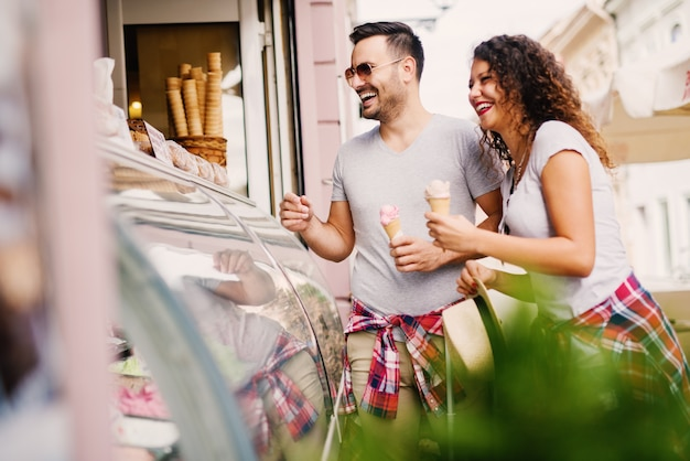 Casal fofo rindo ao comprar sorvete na sorveteria.