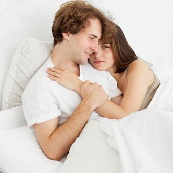 Casal fofo se abraçando na cama tiro médio