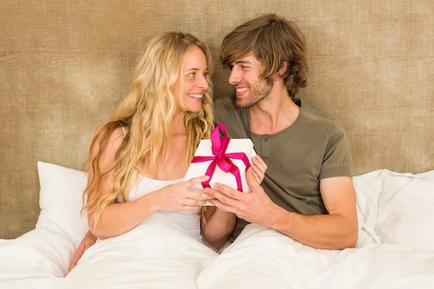 Casal fofo segurando uma caixa de presente na sua cama