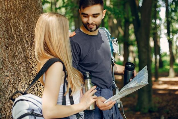 Casal fofo tem um descanso em uma floresta de verão