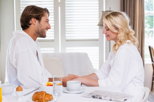 Casal fofo tomando café da manhã em seus roupões de banho