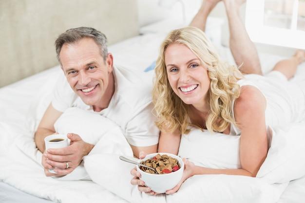 Casal fofo tomando café da manhã na cama no seu quarto