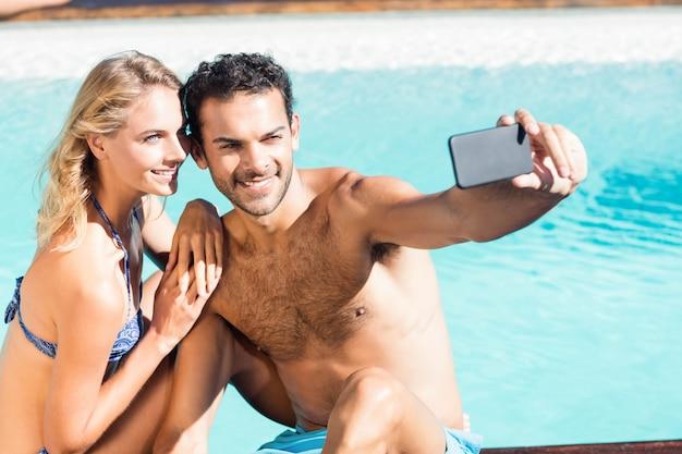 Casal fofo tomando selfie à beira da piscina