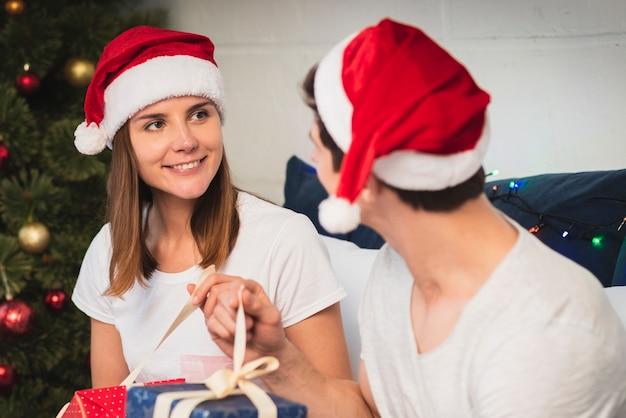 Casal fofo usando chapéus de papai noel, olhando um ao outro