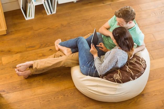 Casal fofo usando o tablet pc no beanbag