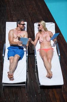 Casal fofo usando tablet e deitado em espreguiçadeiras