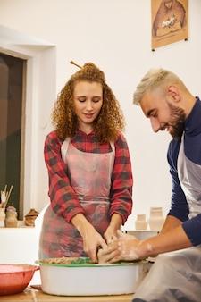 Casal forma um vaso juntos em um local de trabalho de cerâmica